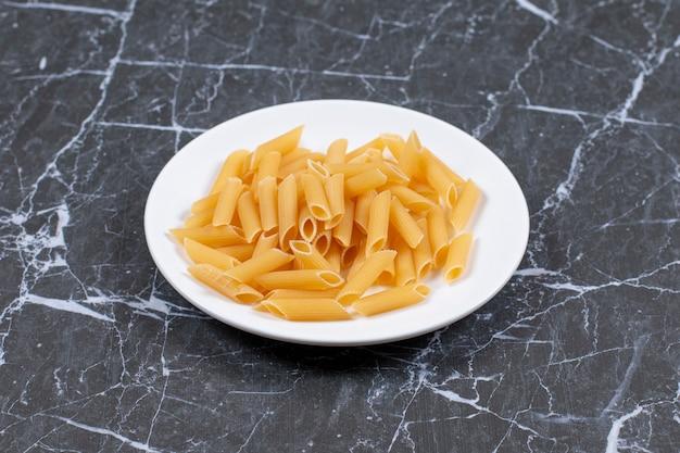 Pasta en plato blanco. pasta cruda sin cocer lista para cocinar.