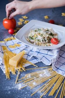 Pasta con pollo, champiñones, crema, pimiento, cebolla, perejil en un plato blanco