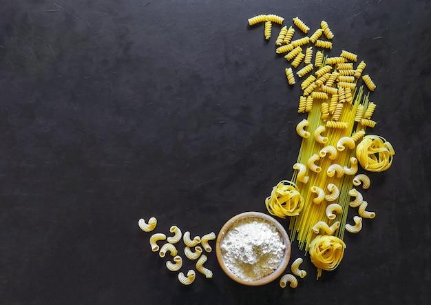 La pasta se presenta en forma de media luna. espaguetis de pasta italiana, tagliatelle, fusilli, cavatappi sobre fondo negro.