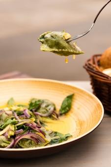 Pasta de ravioles verdes con cebolla y hojas de albahaca en placa
