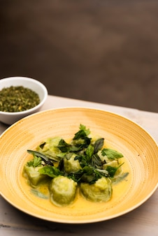 Pasta de ravioles verdes servida en plato con tazón de hierbas