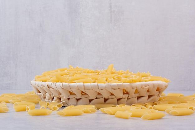 Pasta rigatoni cruda en canasta de madera