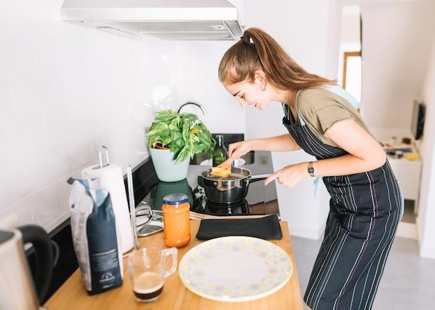 Pasta de rigatoni hirviendo mujer joven en la olla sobre la estufa eléctrica