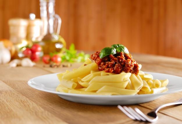Pasta rigatoni con salsa de tomate y ternera sobre la mesa de la cocina