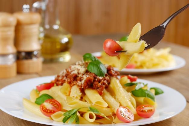 Pasta rigatoni con salsa de tomate y ternera sobre la mesa de roble