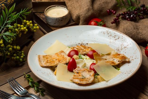Pasta con rodajas de pollo a la parrilla y tomates en un tazón blanco.