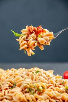 Pasta rotini de vista frontal en un plato y en un tenedor sobre una superficie oscura aislada