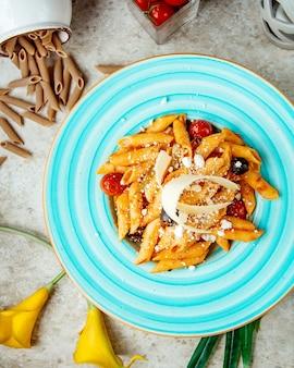 Pasta en salsa de tomate con aceitunas tomate y parmesano rallado vista superior