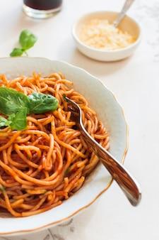 Pasta con salsa de tomate y albahaca en plato cerámico con tenedor