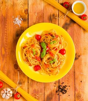 Pasta con salsa de tomate y otros componentes sobre un fondo de madera espacio libre para texto.