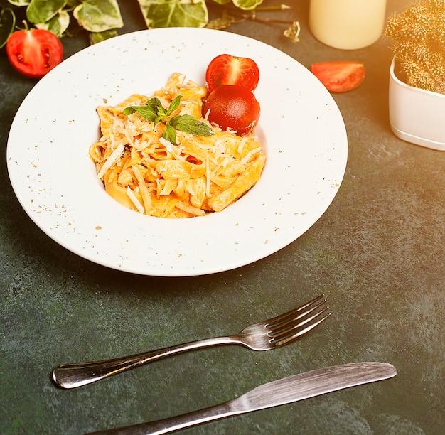Pasta en salsa de tomate con parmesano picado, tomate y albahaca.