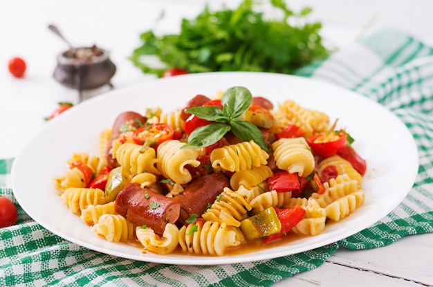 Pasta con salsa de tomate con salchicha, tomate, albahaca verde decorada en plato blanco sobre una mesa de madera.