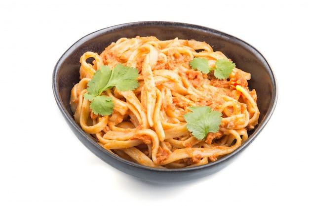 Pasta de sémola con salsa de tomate al pesto, naranja y hierbas aisladas. vista lateral.