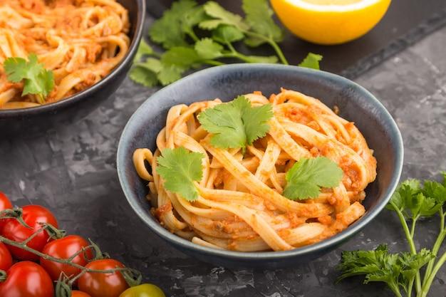 Pasta de sémola con salsa de tomate al pesto, naranja y hierbas. vista lateral