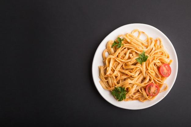 Pasta de sémola con salsa de tomate al pesto, naranja y hierbas. vista superior, copyspace