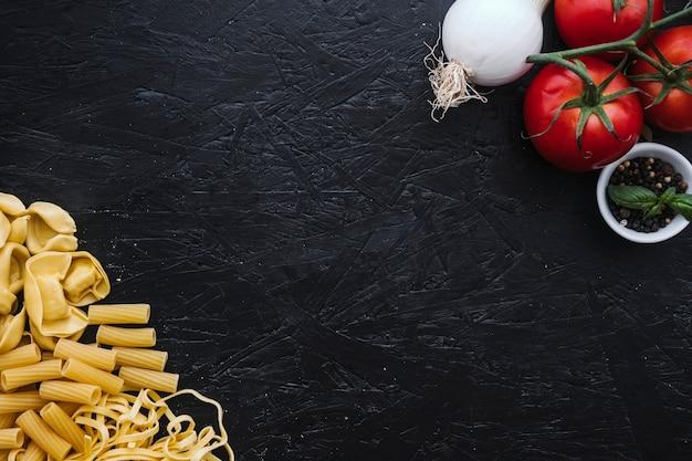 Pasta surtida cerca de verduras y especias