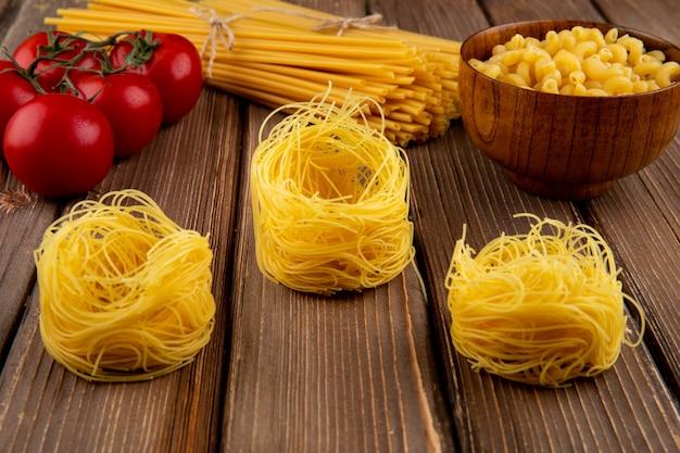 Pasta tagliolini en la mesa de madera tomate chifferi linguini vista lateral