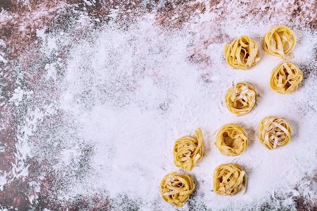 Pasta de tallarines crudos sin cocer en la mesa de la cocina de madera.