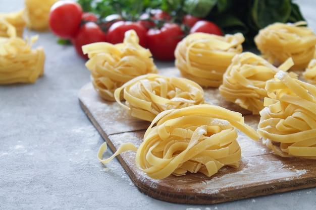 Pasta de tallarines crudos con hierbas frescas y tomates cherry en vista lateral de tablero de madera rústica