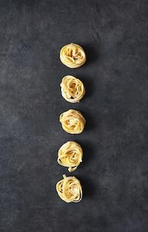 Pasta de tallarines sobre una mesa de hormigón negro. cocinar pasta en la mesa de la cocina.
