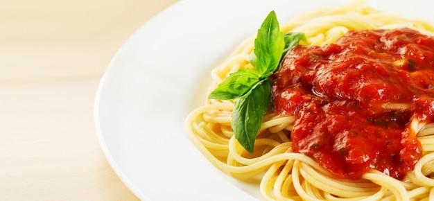 Pasta de tomate servida en plato con albahaca