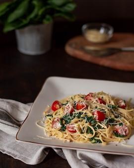 Pasta con tomates espinacas y parmesano