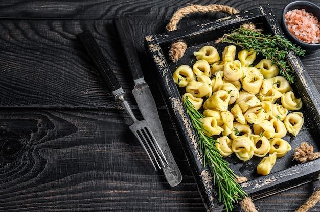 Pasta tortellini tradicional italiana con espinacas en una bandeja de madera.