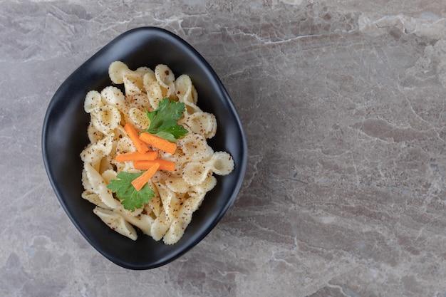 Pasta tradicional italiana con zanahoria finamente picada y verdura verde, sobre el mármol.