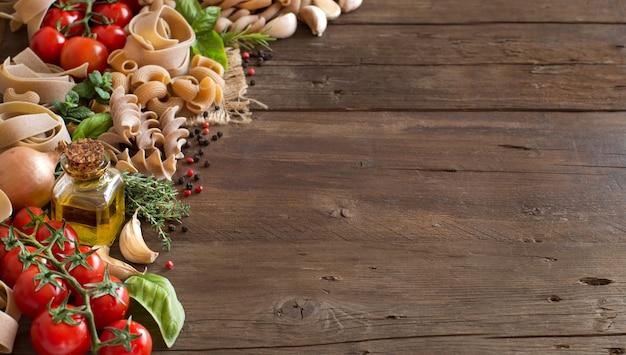 Pasta de trigo integral, verduras, hierbas y aceite de oliva en la mesa de madera de cerca con espacio de copia