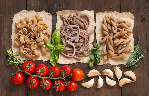 Pasta de trigo integral, verduras, hierbas y aceite de oliva en la mesa de madera