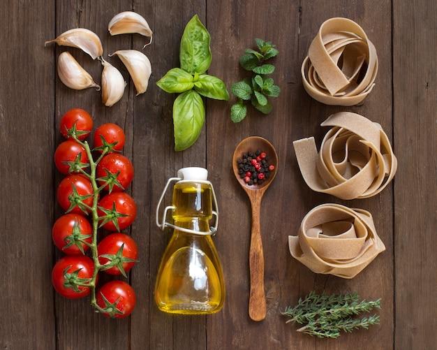 Pasta de trigo integral, verduras, hierbas y aceite de oliva en la vista superior de la mesa de madera