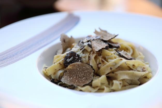 Pasta con trufas negras sobre fondo de madera, comida italiana