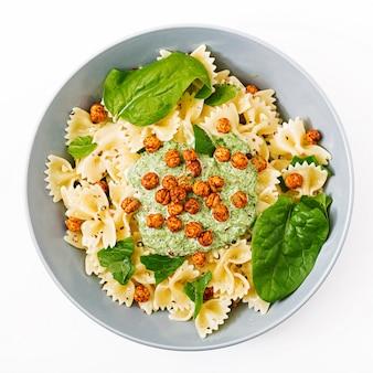 Pasta vegana farfalle con salsa de espinacas y garbanzos fritos.