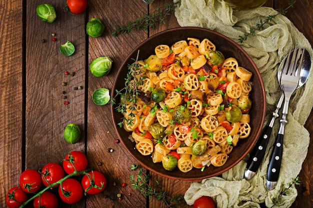 Pasta de verduras vegetariana rocchetti con coles de bruselas, tomate, berenjena y pimentón en un tazón marrón sobre mesa de madera. vista superior