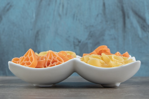 Pastas sin cocer en forma de corazón y arco en la placa blanca.