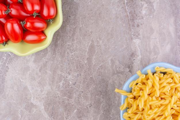 Pastas crudas y tomates cherry rojos en espacio gris.