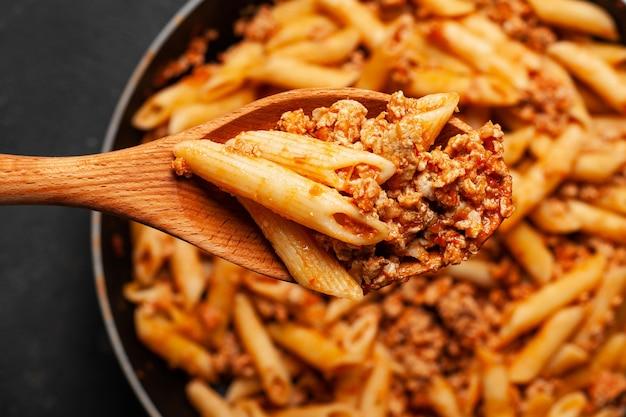 Pastas italianas frescas del penne boloñés en la cuchara de madera.