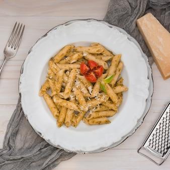 Pastas italianas sabrosas gastrónomas del penne con el tomate y las hierbas en una placa blanca