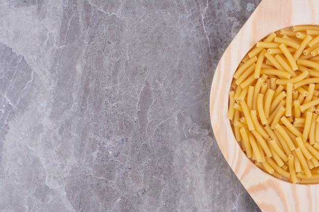 Pastas orgánicas en una taza de madera rústica en el espacio gris.