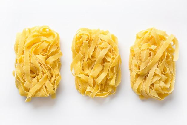 Las pastas sabrosas forman reginelle en blanco. aislado. tablero con harina. vista desde arriba.