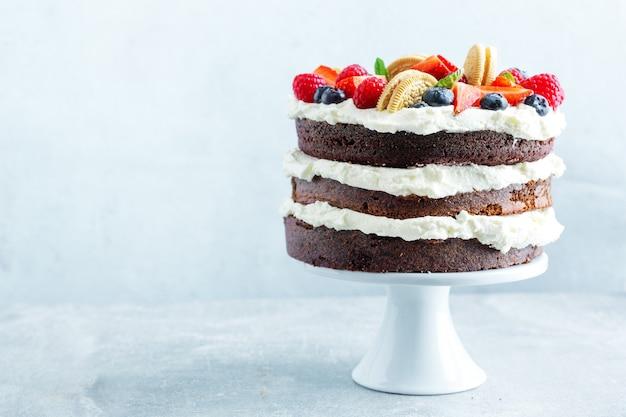 Pastel afrutado con frutas frescas y crema en soporte sobre fondo brillante.