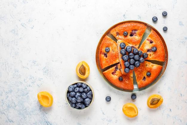 Pastel de albaricoque y arándano con arándanos frescos y frutas de albaricoque.