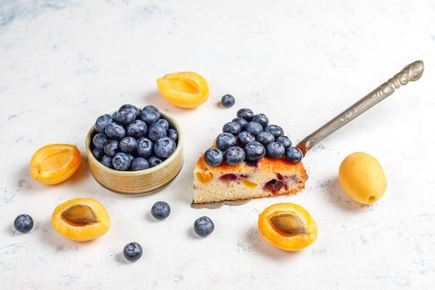 Pastel de albaricoque y arándanos con arándanos frescos y frutas de albaricoque.