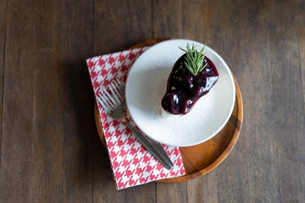 Pastel de arándanos en un plato colocado sobre una mesa de madera