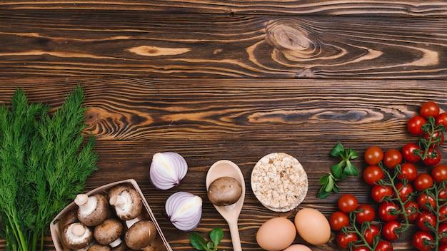 Pastel de arroz inflado redondo con verduras frescas en madera con textura