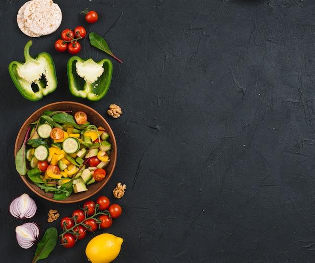 Pastel de arroz inflado; vegetales; ensalada y nuez sobre encimera de cocina negra.