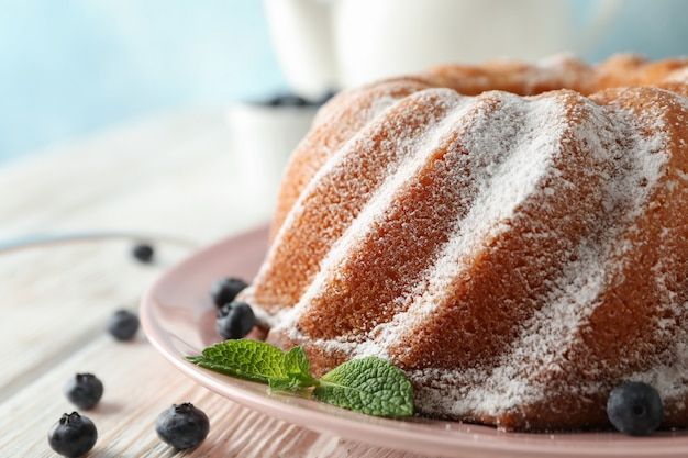 Pastel con azúcar en polvo y arándanos sobre fondo de madera