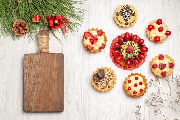 Pastel de bayas de vista superior redondeado con tartas hojas de pino con juguetes navideños y una tabla de cortar en el suelo de madera blanca