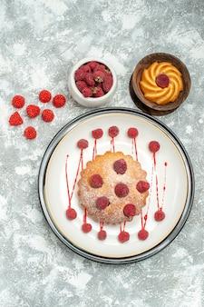 Pastel de bayas de vista superior en tazón de galleta plato ovalado blanco con frambuesas en superficie gris