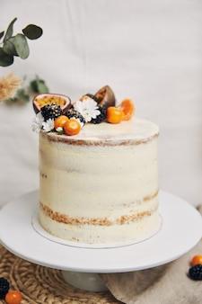 Pastel blanco con bayas y maracuyá junto a una planta detrás de un fondo blanco.